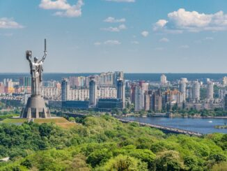 motherland monument among green trees on embankment in kiev